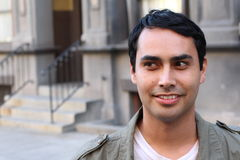 Closeup portrait of a happy Hispanic/Spanish man looking to left. Against urban background Stock Photos