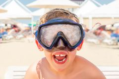 Closeup portrait of a happy laughing boy with diving mask at a sunny beach. royalty free stock photo