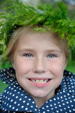 Closeup portrait  happy little girl in grass wreath. Smiling Royalty Free Stock Image
