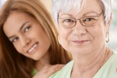 Closeup portrait of happy mother and daughter. Closeup portrait of happy senior mother and young daughter, hugging, smiling Stock Photography