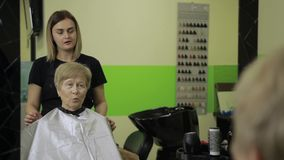 Happy woman looking at her haircut in hair salon stock video footage