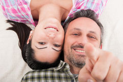 Closeup portrait of happy smiling couple in love. Laying down while male pointing finger up Royalty Free Stock Photo