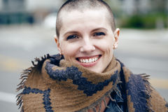 Closeup portrait of happy smiling laughing beautiful Caucasian white young bald girl woman with shaved hair head. In leather jacket and scarf shawl looking in Royalty Free Stock Photography