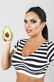 Closeup portrait of happy woman holding a fresh avocado in her h Royalty Free Stock Images