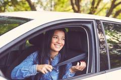 Closeup portrait of happy woman pulling on seatbelt Stock Image