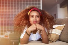 Closeup portrait of a happy young American African girl with long curly hair relaxing and have fun alone on sofa at. Modern home royalty free stock photo