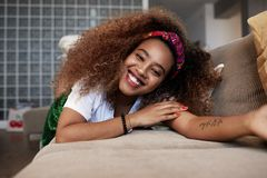 Closeup portrait of a happy young American African girl with long curly hair relaxing and have fun alone on sofa at. Modern home stock images