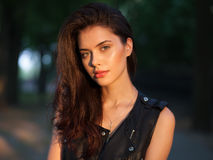 Closeup portrait of happy young beautiful brunette woman in black leather jacket posing on sunset outdoors  with blurry foliage ba Stock Images