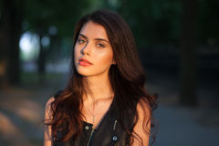 Closeup portrait of happy young beautiful brunette woman in black leather jacket posing on sunset outdoors  with blurry foliage ba Stock Image
