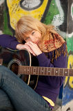 Closeup portrait of a happy young girl with guitar. And graffiti on background Royalty Free Stock Photos