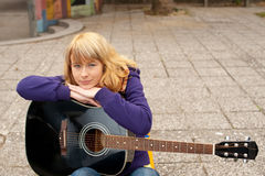 Closeup portrait of a happy young girl with guitar. Beautiful youg woman playing a guitar outdoor Royalty Free Stock Images