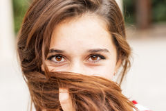 Closeup portrait of happy young woman covers her face of hair. Royalty Free Stock Photography