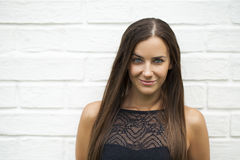 Closeup portrait of a happy young woman smiling. Against a white brick wall, summer outdoors Royalty Free Stock Image