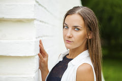 Closeup portrait of a happy young woman smiling. Against a white brick wall, summer outdoors Royalty Free Stock Photography