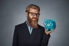 Man smiling holding Piggy bank both wearing glasses isolated on gray royalty free stock photo