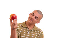 Closeup portrait of a healthy young man holding and offering an apple Royalty Free Stock Images