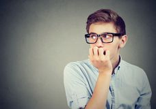 Closeup portrait hesitant nervous man biting his fingernails craving something anxious. Isolated on gray wall background. Negative human emotions feeling Royalty Free Stock Image