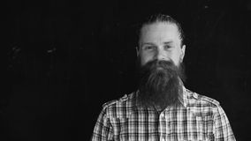 Closeup portrait of hipster man looking at camera and smiling on black background Royalty Free Stock Images