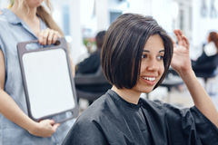 Closeup portrait of hispanic latin girl woman sitting in chair in hair salon Royalty Free Stock Images