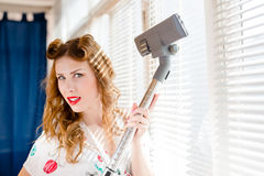 Closeup portrait of holding dust removal vacuum cleaner & having fun beautiful blond young woman happy smiling Royalty Free Stock Photo