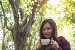 A beautiful Asian woman holding a white mug and drinking hot coffee with feeling happy in green nature background. Closeup portrait image of a beautiful Asian Stock Photos