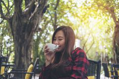 A beautiful Asian woman holding a white mug and enjoy drinking hot coffee with feeling happy in green nature background. Closeup portrait image of a beautiful Royalty Free Stock Images