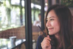 Closeup portrait image of a beautiful Asian woman with smiley face sitting in modern cafe while thinking about business Stock Image