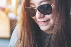 Woman wearing black sunglasses. Closeup portrait image of a smiley beautiful Asian woman wearing black sunglasses with feeling good sitting and relaxing in Stock Image