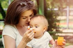 Closeup portrait of a infant baby eating vegetable puree from spoon. Mother feeding little child outdoor on a walk in summer day royalty free stock photos