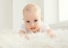 Closeup portrait of infant lying at home in white room Stock Images