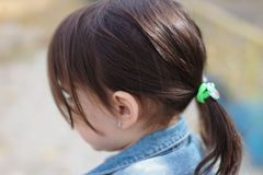 closeup portrait of little cute emotional girl with pigtails in a denim jacket stock photo