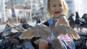 Closeup portrait of little cute girl feeding street pigeons in the park. At summer day royalty free stock image