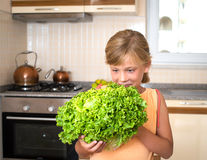 Closeup portrait of little girl holding fresh green lettuce in the kitchen. Healthy food and lifestyle concept. stock image