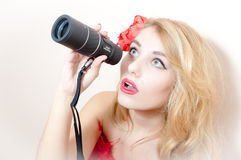 Closeup portrait on looking peering in spyglass telescope beautiful glamor young blond pinup woman attractive girl having fun Royalty Free Stock Image