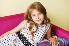 Portrait of a lovely little girl in polka dot dress resting on p. Closeup portrait of a lovely little girl in polka dot dress resting on purple sofa royalty free stock photo