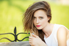 Closeup portrait of lovely urban girl outdoors. Happy smiling woman. Fashionable blonde girl sitting on a bench in a city park Stock Images