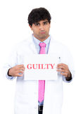 Closeup portrait of male health care professional, doctor or nurse holding up guilty sign, Royalty Free Stock Image