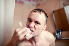 Closeup portrait man brushes teeth in bathroom an electric brush and grimace to play the fool Stock Photos