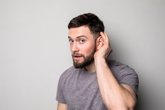 Closeup portrait a man placing hand on ear listening carefully isolated on gray wall background. stock image