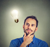 Closeup portrait man thinks looking up at bright light bulb Royalty Free Stock Photography