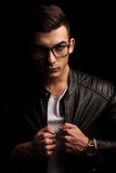 Closeup portrait of man wearing glasses, pulling black leather j Royalty Free Stock Photo