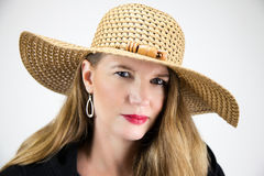 Closeup Portrait Mature Blonde Female in Hat and Black Coat Looking at Camera royalty free stock images