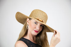 Closeup Portrait Mature Blonde Female with Holding Hat Wearing Black Top Looking At Camera stock photo