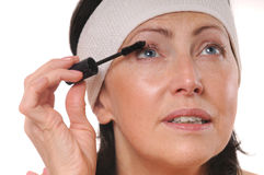 Closeup portrait of mature woman applying mascara on eyelashes. 50-year-old woman put mascara in front of mirror Stock Photos