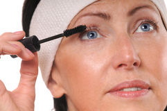 Closeup portrait of mature woman applying mascara on eyelashes. 50-year-old woman put mascara in front of mirror Royalty Free Stock Photography