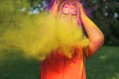 Closeup portrait of merry blonde girl having fun in a cloud of yellow and purple dry Holi paint stock image