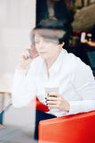 Closeup portrait of middle age Caucasian white business woman sitting in cafe restaurant with cup of coffee talking over on phone Stock Photos