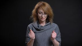 Closeup portrait of middle-aged extravagant redhead female in glasses being worried and nervous clenching her fists in royalty free stock images