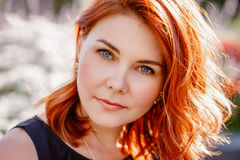 Closeup portrait of middle aged white caucasian woman with waved curly red hair with blue eyes. In black dress, looking in camera, outside in park, beauty royalty free stock photo