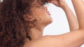 Mixed race black woman with freckles and curly hair in studio on white poses to a camera. Closeup portrait of mixed race model with freckles touching her hair stock video